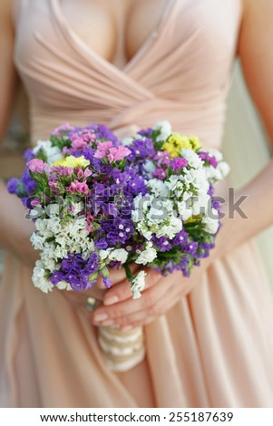 beautiful wedding bouquet of multicoloured statice flowers in hands of the bride - stock photo
