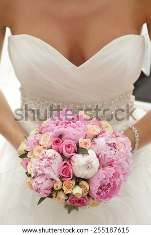 Beautiful wedding bouquet of pink and beige roses, paeonies in hands of the bride - stock photo