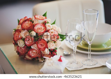 Beautiful wedding bouquet of pink and white rose on table with wineglasses