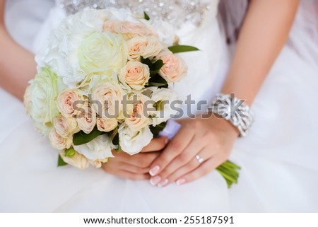 beautiful wedding bouquet of roses and eustoma flowers in hands of the bride - stock photo
