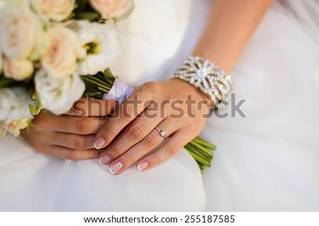 beautiful wedding bouquet of roses and eustoma flowers in hands of the bride, french manicure - stock photo