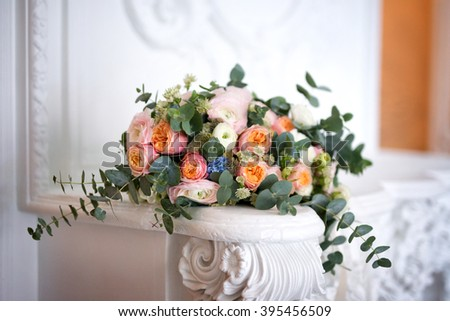 Beautiful wedding bouquet on a white fireplace.  Bouquet consists of pink and white roses, eucalyptus.