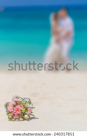 beautiful wedding bouquet on bride and groom background, outdoor beach wedding - stock photo