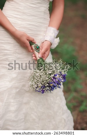 Beautiful wedding bouquet with a vintage brooch of flowers in hands of the bride - stock photo