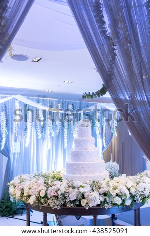 beautiful wedding cake at wedding reception. white wedding cake with flower  colorful decorated on wooden plate with flowers, decoration, bokeh curtain on Led light background. in Wedding room party. - stock photo