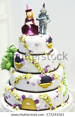 Beautiful Wedding cake decorated with knight and princess for party - stock photo