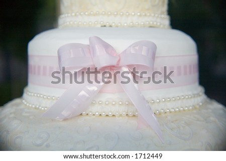 Beautiful wedding cake with a pink bow - stock photo