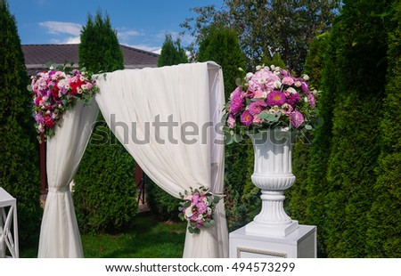 Beautiful wedding ceremony under the open sky on a green lawn. Wedding decor: the wedding arch decorated with fresh flowers and white fabric, volume compositions of fresh flowers in big white vases.