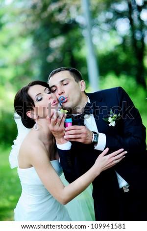 beautiful wedding couple blowing bubbles - stock photo