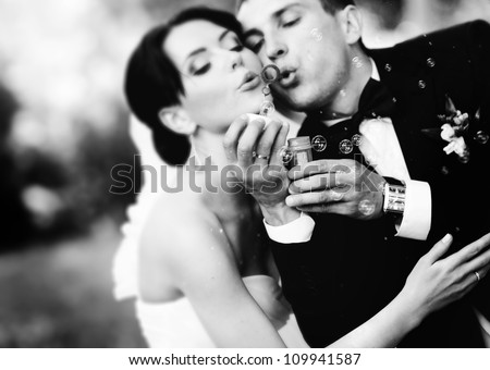 beautiful wedding couple blowing bubbles