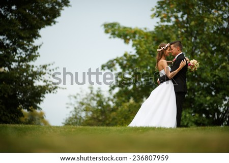 Beautiful wedding couple. Bride and groom. Beautiful young loving couple hugging and looking at each other while standing outdoors. Bride and Groom at wedding day walking Outdoors on spring nature.