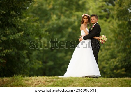Beautiful wedding couple. Bride and groom. Beautiful young loving couple hugging and looking at each other while standing outdoors. Bride and Groom at wedding day walking Outdoors on spring nature. - stock photo