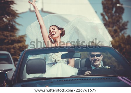 Beautiful wedding couple in car - stock photo