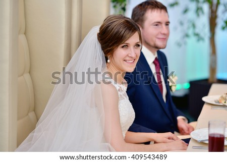 Beautiful wedding couple in restaurant. White decor for bride and groom. Colorful decoration for celebration. Beauty bridal interior for marriage. Bouquet, food and flowers in hall