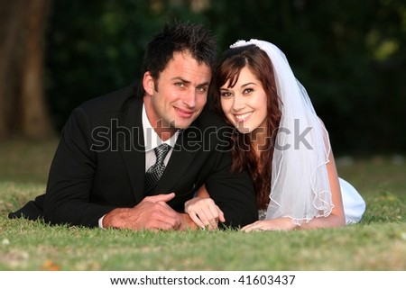 Beautiful wedding couple laying down outdoors on the grass