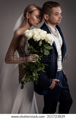 Beautiful wedding couple posing together. Blonde woman with long hair. Handsome man in suit. Studio shot. - stock photo