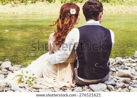 Beautiful wedding couple sitting on stone coast near river. Husband hugs his wife. - stock photo