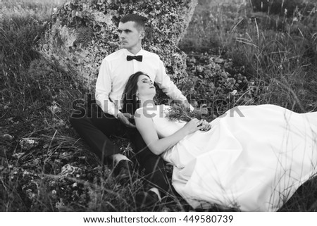 Beautiful wedding couple sitting outdoors near a large stone. Groom loves bride.