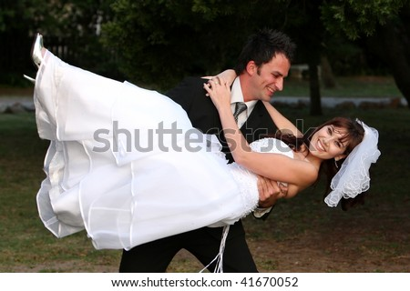 Beautiful wedding couple with groom lifting his smiling bride