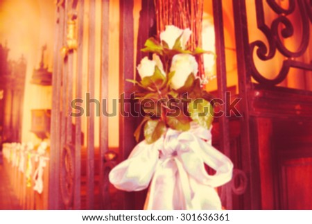 Beautiful wedding decoration with white roses in the church. Retro toned image. Blurred unfocused photo.