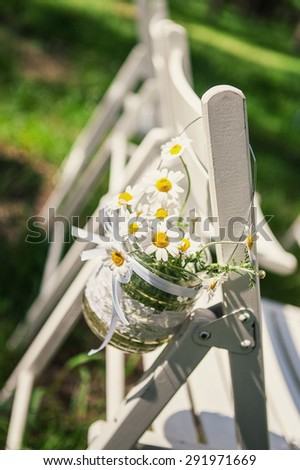 Beautiful wedding decorations in the form of daisies that hang on a chair