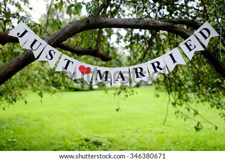 Beautiful wedding inscription 'just married' on the nature. Close-up beauty of colored placard. Bridal accessories. Female and male decoration for couple. Details for marriage - stock photo