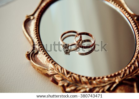 Beautiful wedding rings on a vintage mirror  - stock photo