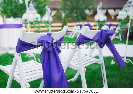 beautiful wedding setting, chair tied with purple ribbon