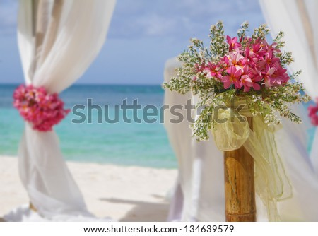 beautiful wedding setup and flowers on tropical beach background - stock photo
