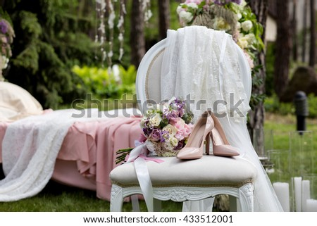 Beautiful wedding shoes with high heels and a bouquet of colorful flowers on a vintage chair on the nature in sunset light, decorations, preparing for the wedding, details, boudoir - stock photo