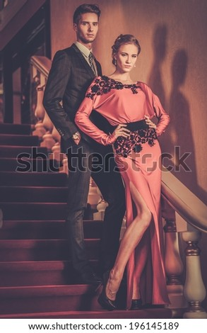 Beautiful well-dressed young couple standing on a steps in luxury interior - stock photo