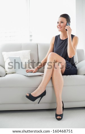 Beautiful well dressed young woman using laptop and cellphone on sofa at bright home - stock photo