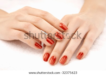 Beautiful well-groomed female hands with the red manicure, isolated - stock photo