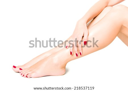 Beautiful well-groomed female legs with red pedicure isolated on white background - stock photo