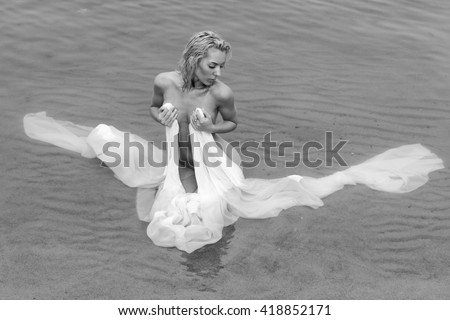 beautiful wet blonde wrapped up by white fabric sits in water on a beach - stock photo