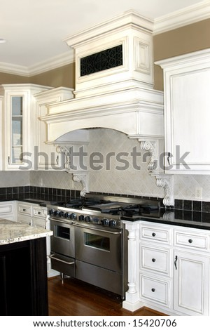 Beautiful white and black kitchen with painted wooden cabinets and wood flooring.