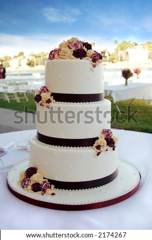 Beautiful White and Burgundy Wedding Cake With Flowers - stock photo