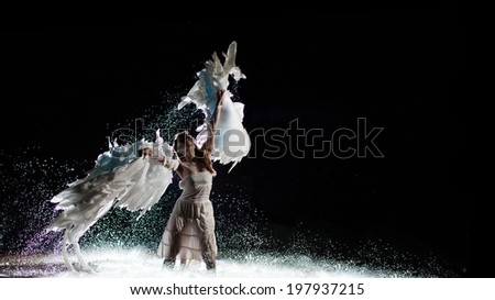 Beautiful white angel is dancing in the water drops. - stock photo
