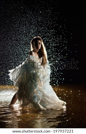 Beautiful white angel is standing in the water. - stock photo