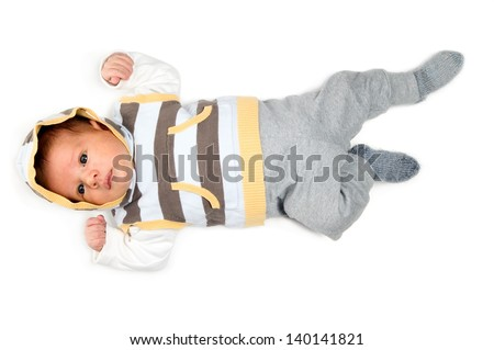 Beautiful white baby boy with big eyes is lying on white background
