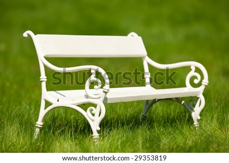 Beautiful white bench in green meadow in spring - stock photo