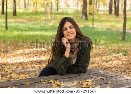 Beautiful white caucasian girl with blue eyes among trees in the forest. She is sitting in a chair in a bench.