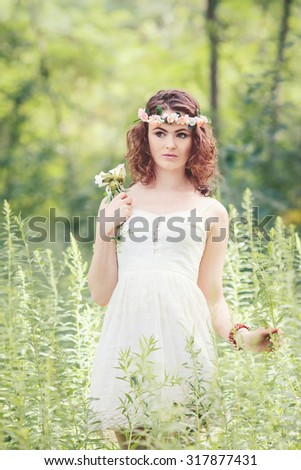 Beautiful white Caucasian girl with hazel eyes, long wavy curly hair and flowers chaplet on head. Attractive young woman model in park outside, country village hippie style - stock photo