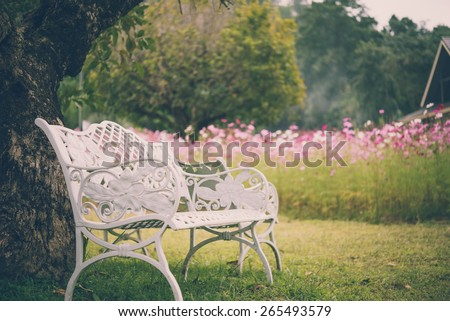 Beautiful white chairs under tree in garden, Thailand - Vintage effect style - stock photo