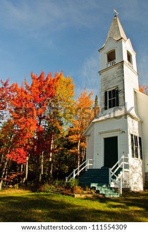 Beautiful white church and New England Fall colors. - stock photo