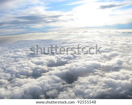 Beautiful white clouds under sunshine, shot on a airplane, above the clouds, blue sky - stock photo