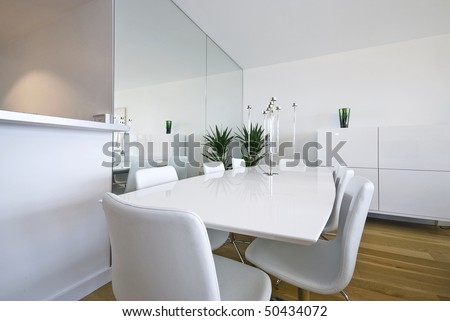 Beautiful white dining area with massive dining table and chairs for eight - stock photo
