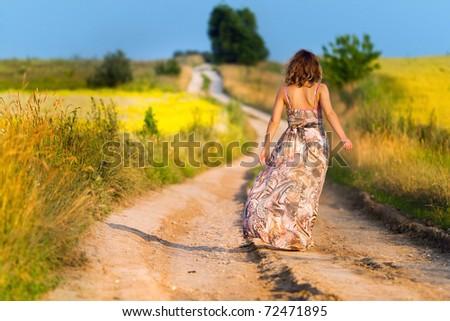 Beautiful white girl walking the road before sunset - stock photo