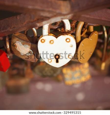 beautiful white heart-shaped padlock locked on iron chain, romance concept, square - stock photo