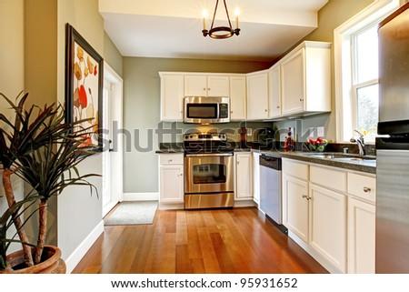 Beautiful white kitchen with cherry floor. - stock photo